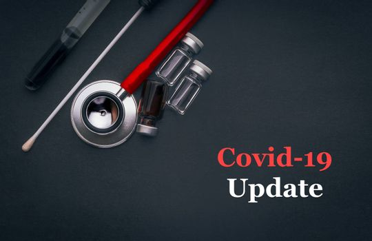 COVID-19 or CORONAVIRUS UPDATE text with stethoscope, medical swab and vial on black background. Covid-19 or Coronavirus concept.
