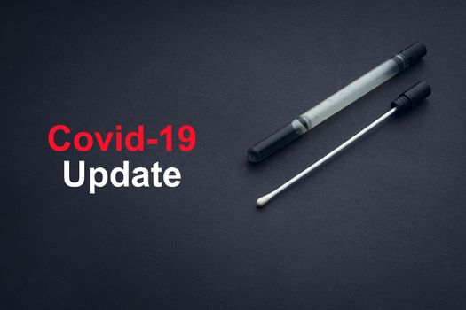 COVID-19 or CORONAVIRUS UPDATE text with medical swab on black background. Covid-19 or Coronavirus concept.