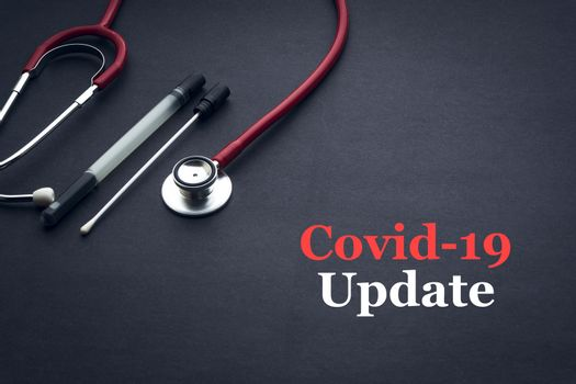 COVID-19 or CORONAVIRUS UPDATE text with stethoscope and medical swab on black background. Covid-19 or Coronavirus concept.