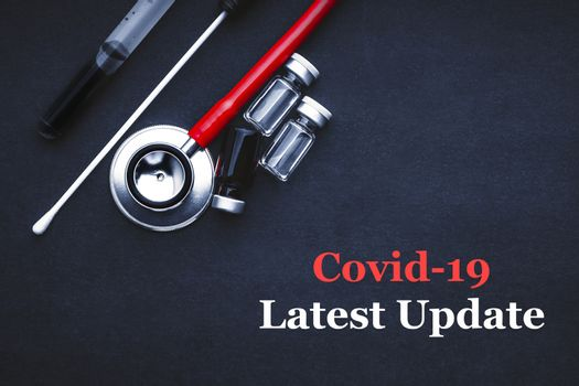 COVID-19 or CORONAVIRUS LATEST UPDATE text with stethoscope, medical swab and vial on black background. Covid-19 or Coronavirus concept.