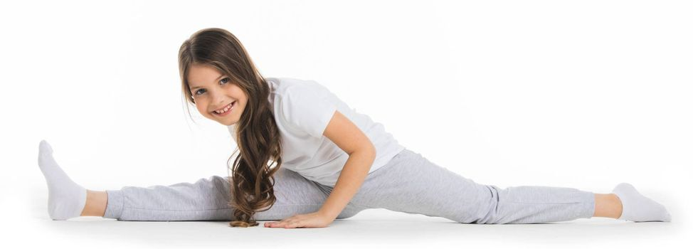 Little cute girl sitting in the splits, isolated on white background