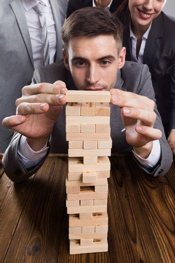 Business people team building wood puzzle tower cooperation concept