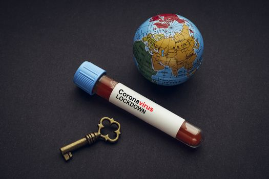 CORONAVIRUS LOCKDOWN text with world globe, key and Blood test vacuum tube on black background. Covid-19 or Coronavirus Concept