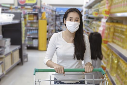 Asian woman wear face mask push shopping cart in suppermarket departmentstore. Girl choosing, looking grocery to buy  something. During coronavirus crisis or covid19 outbreak. Women wearing protective face mask hold shopping cart, New normal after covid epidemic