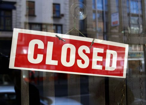 Closed sign a in shop window with blurred background reflections