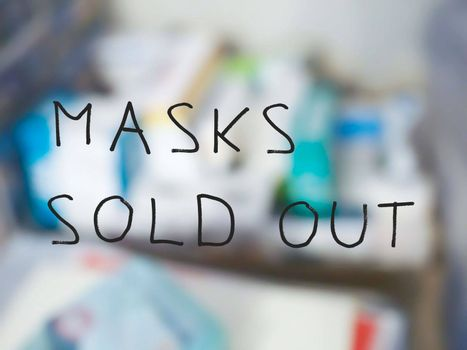 masks sold out sign on pharmacy shop window, with out of focus background of medicines and drugs