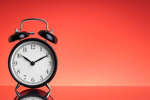 Alarm Clock on red background with selective focus and crop fragment. Business and Copy space concept