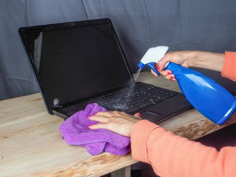 Hands of asian adult woman cleaning and sanitizing home office devices and objects to prevent corona covid-19 virus contagion infection
