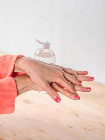 close up of  woman hands while cleaning and sanitizing  herself  with anti virus bacterial gel against covid-19 , fall dress, orange color over a wood table, earth tones.