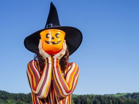 Young woman holding pumpkin bucket for Halloween