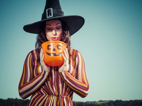 Young woman looking in plastic pumpkin