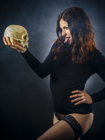 Redhead woman sticking out her tongue at skull