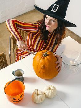 Redhead woman cutting a pumpkin for Halloween