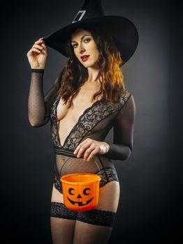 Sexy woman in lingerie holding Halloween pumpkin bucket