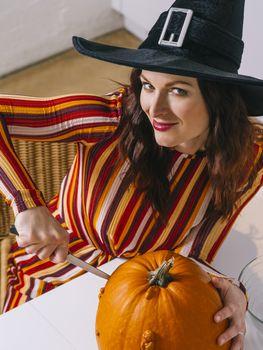 Beautiful woman cutting a pumpkin for Halloween