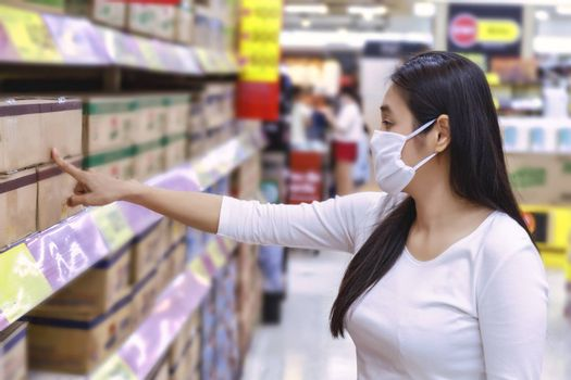 Asian woman wear protect face mask shopping something in grocery department store. Girl point and read something in supermarket during coronavirus crisis, covid19 outbreak. New normal after covid-19