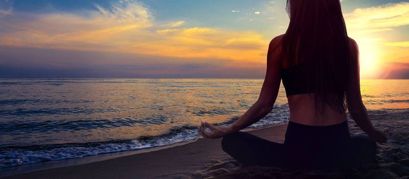 Yoga meditation banner - woman in a lotus pose on a seaside beach on a background of a picturesque sunset landscape (copy space)