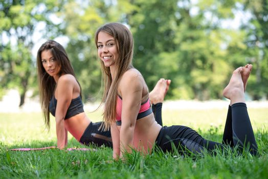 Two beautiful and happy young women doing yoga exercises and in the park on a sunny day in close-up