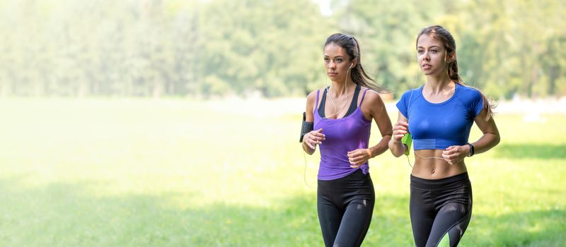 Healthy lifestyle banner - two beautiful fitness girls are jogging in the park on a sunny morning (copy space)