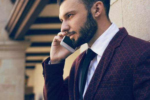 Handsome and fashionable man with a beard talking on the phone in close-up