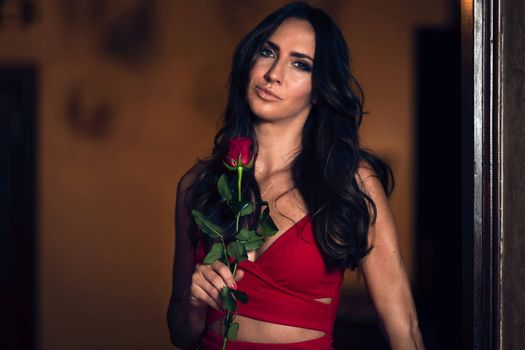 Portrait of a beautiful and elegant woman holding a rose in an evening red dress