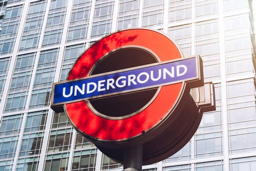 London, England - April 3, 2017: The London Underground sign outside the Canary Wharf Station in Financial District.The London 'Underground' logo will be used for other transportation systems.