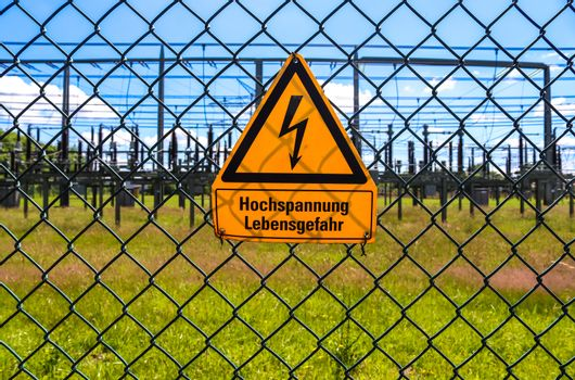 Sign showing the words high voltage in german language at the fe