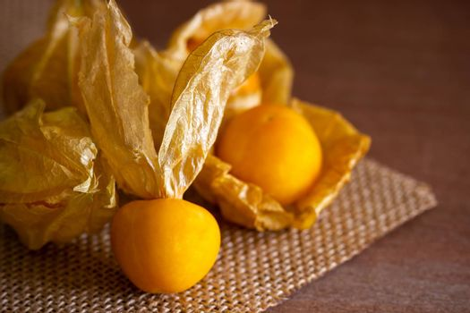 Closeup cape gooseberry on wooden table. Concept of health care or herb.