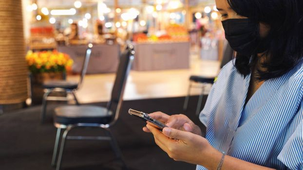 Asian woman using smartphone and sitting separated chair in shopping mall for social distancing to protect covid-19 and coronavirus outbreak, a new normal lifestyle concept