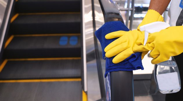 Staff cleaning the escalator hand rail in department store to prevent the spread of pandemic Covid-19 and Coronavirus, healthcare and hygiene concept