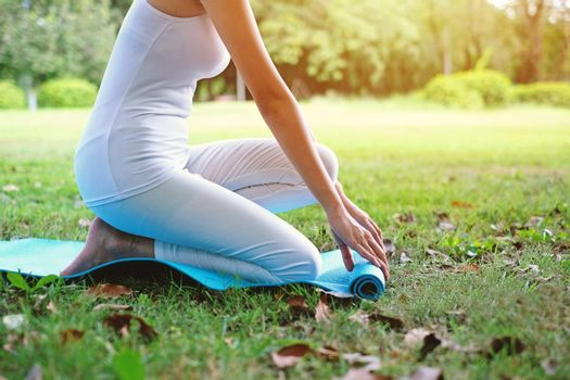 Close up of attractive young woman rolling up fitness mat on green grass in the park, preparing for working out in the morning