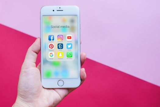 BANGKOK, THAILAND - NOVEMBER 28, 2016:  Hand holding Apple iPhone 6s screen showing group of popular social networks icons on pink and red background, Social media are most popular tool for communication.