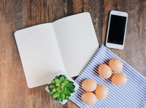 Flat lay design of notebook, smartphone, plant and eggs on wooden table background, spring concept