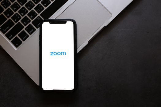 BANGKOK, Thailand - April 2, 2020 : Flat lay of iPhone showing zoom application and laptop on black background. Zoom is popular cloud meeting or video conference during COVID-19 and Coronavirus