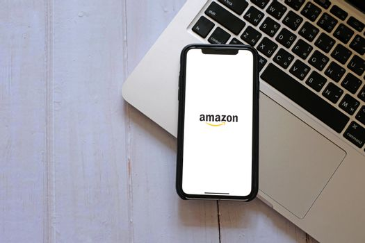 BANGKOK, Thailand - April 2, 2020 : Flat lay of iPhone showing amazon application and laptop on wooden background. Amazon is popular shopping online retailer during COVID-19 and Coronavirus