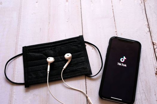 BANGKOK, Thailand - April 2, 2020 : Flat lay of iPhone XS showing Tik Tok application on screen with earphones and black mask on wooden table, Tik tok is popular social media network
