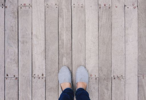 Selfie of feet and shoes on wooden floor background with copy space, top view