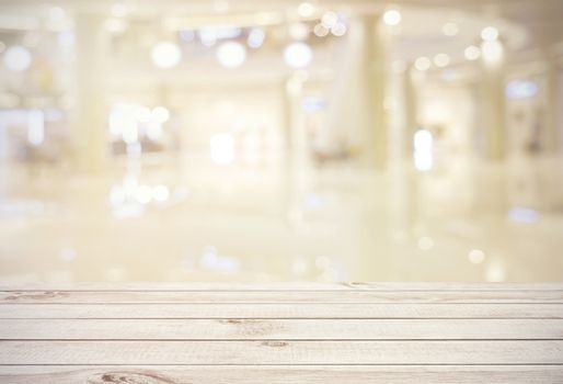 Empty wooden board table top on blur abstract of shopping mall background, for montage product or display, mock up for display of product