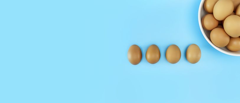 Top view Fresh chicken eggs in white bowl and chicken eggs on blue background with copy space. Uncooked raw eggs in bowl isolated banner.
