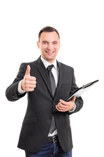 Handsome confident smiling businessman in a suit standing, holding a clipboard and giving thumb up gesture, isolated on white background. Young attractive businessman wearing a suit and tie giving thumb up.