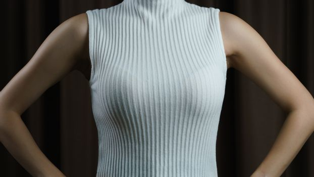 The women with white sleeveless shirt on black background.