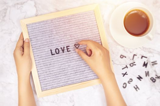 word LOVE on letter board with woman's hand holding heart symbol on white marble desk background with coffee cup