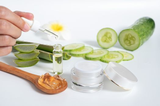 organic natural skincare concept. open blank cosmetic cream jar with white cream texture inside and women hand holding glass dropper for dermatologist testing decorate with aloe vera and cucumber