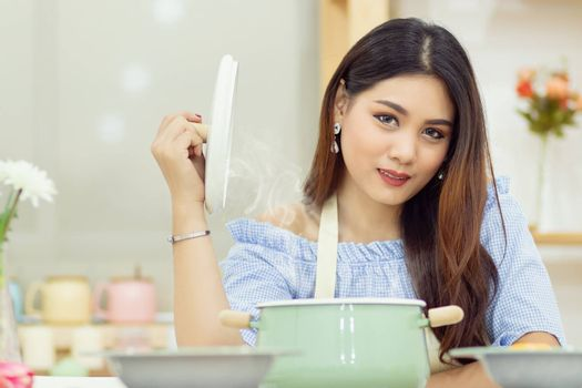 beautiful Asian woman sit at the table in the kitchen, open the lid of the soup pot with the heat vapor floating up.