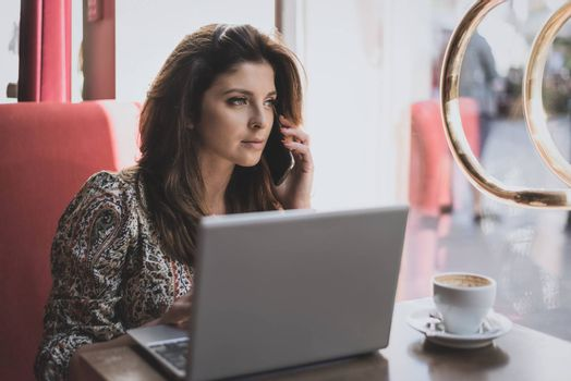 Beautiful young business woman working while drinking coffee in the restaurant.