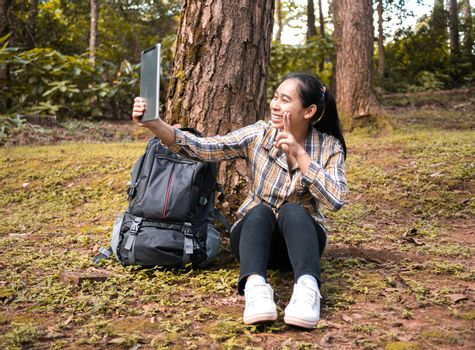 Young woman traveler selfie by using tablet while sit and rest in forest on summer vacations day. Lifestyle hiking concept.