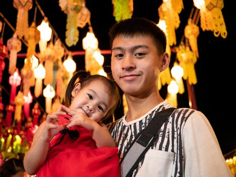 Happy Asian family standing over light from Thai lanna lanterns background at night in Yi Peng Festival.