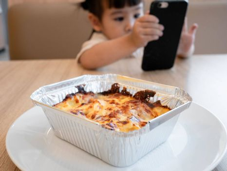 Little Asian child girl eating lunch while watching cartoon on the smartphone in a restaurant with her family. Child addicted to mobile phones.