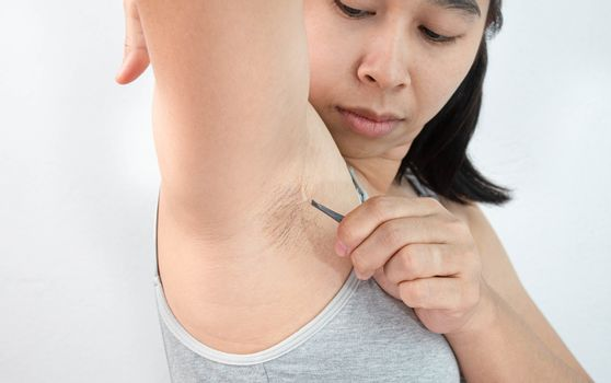 Close up of young woman plucking armpit underarm with tweezers isolated on grey background. Concept of Hygiene skin body care and beauty.