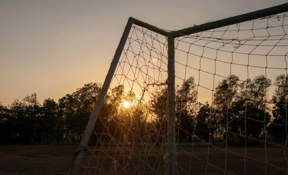 Football goal with sunset light background in the public stadium.
